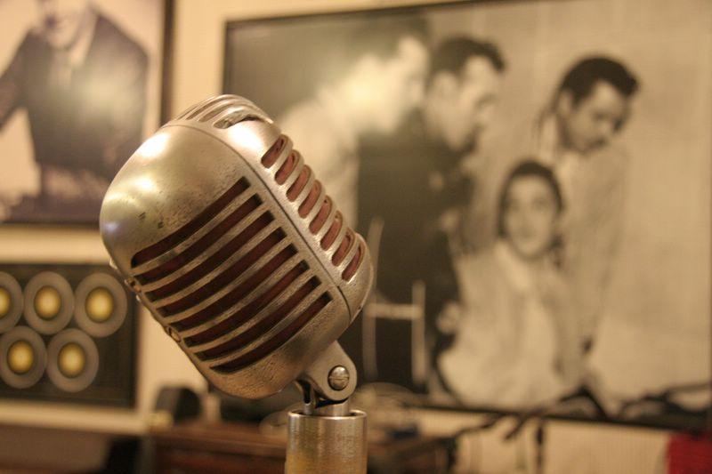 Dietro ad un microfono anni '50 si intravvede il poster