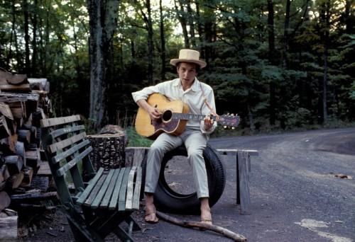 Una foto di Bob Dylan seduto tra il verde dell'area di Big Pink