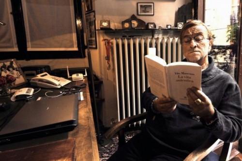 Lucio all'interno di casa mentre legge un libro