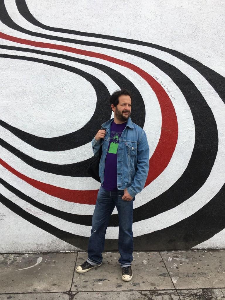 Marco in posa davanti al murales
